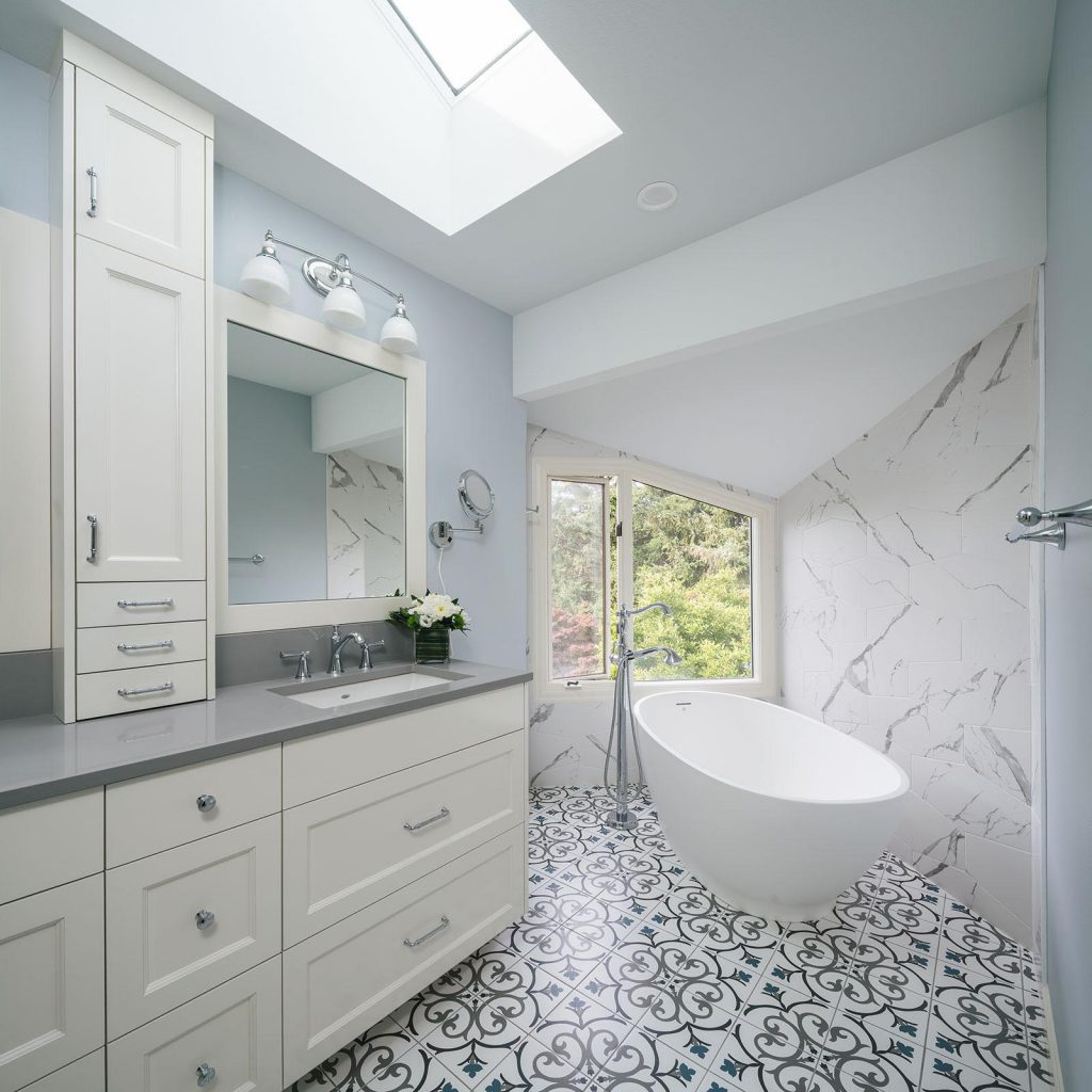 remodeled bathroom with white cabinets and a big white bathtub