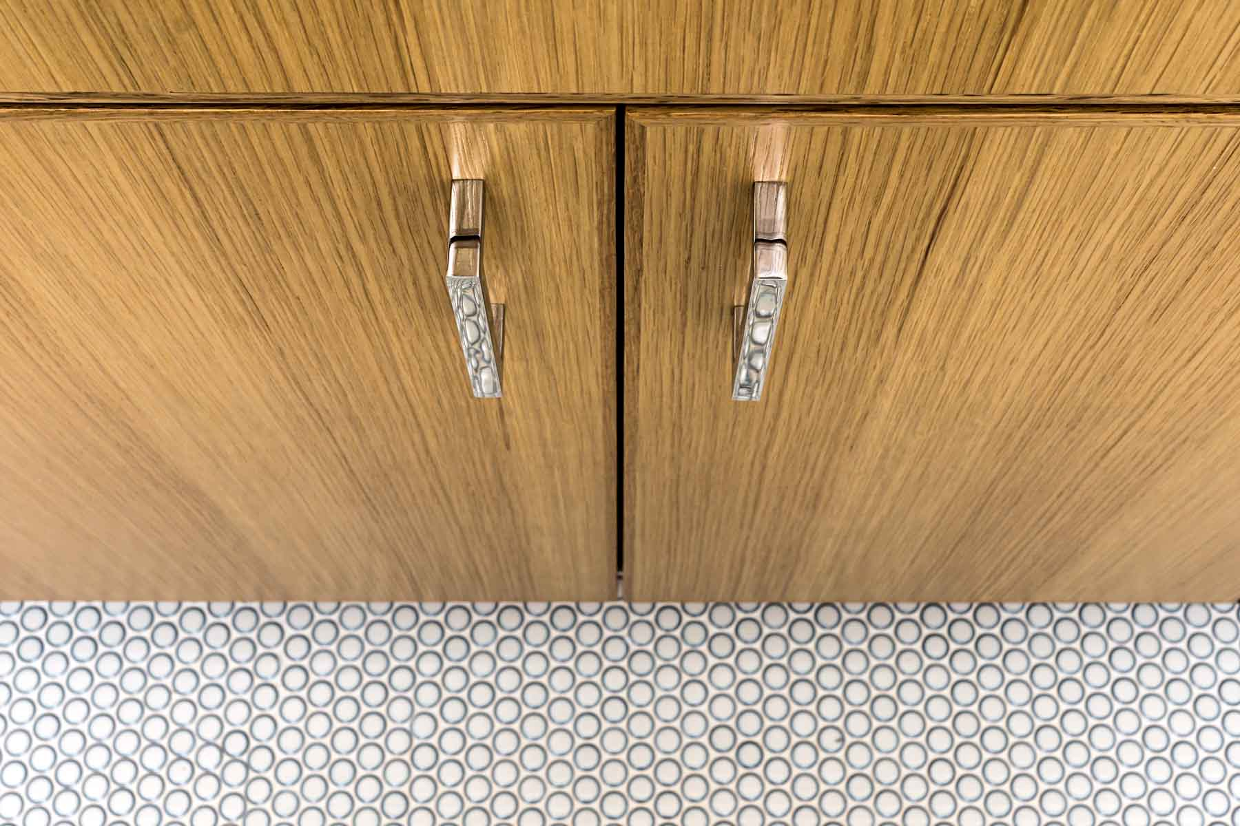 Wood cabinets with small white floor tiles in kitchen remodel