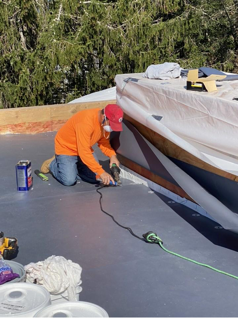 PhotHamish Murrary Construction Inc worker installing roof membrane.