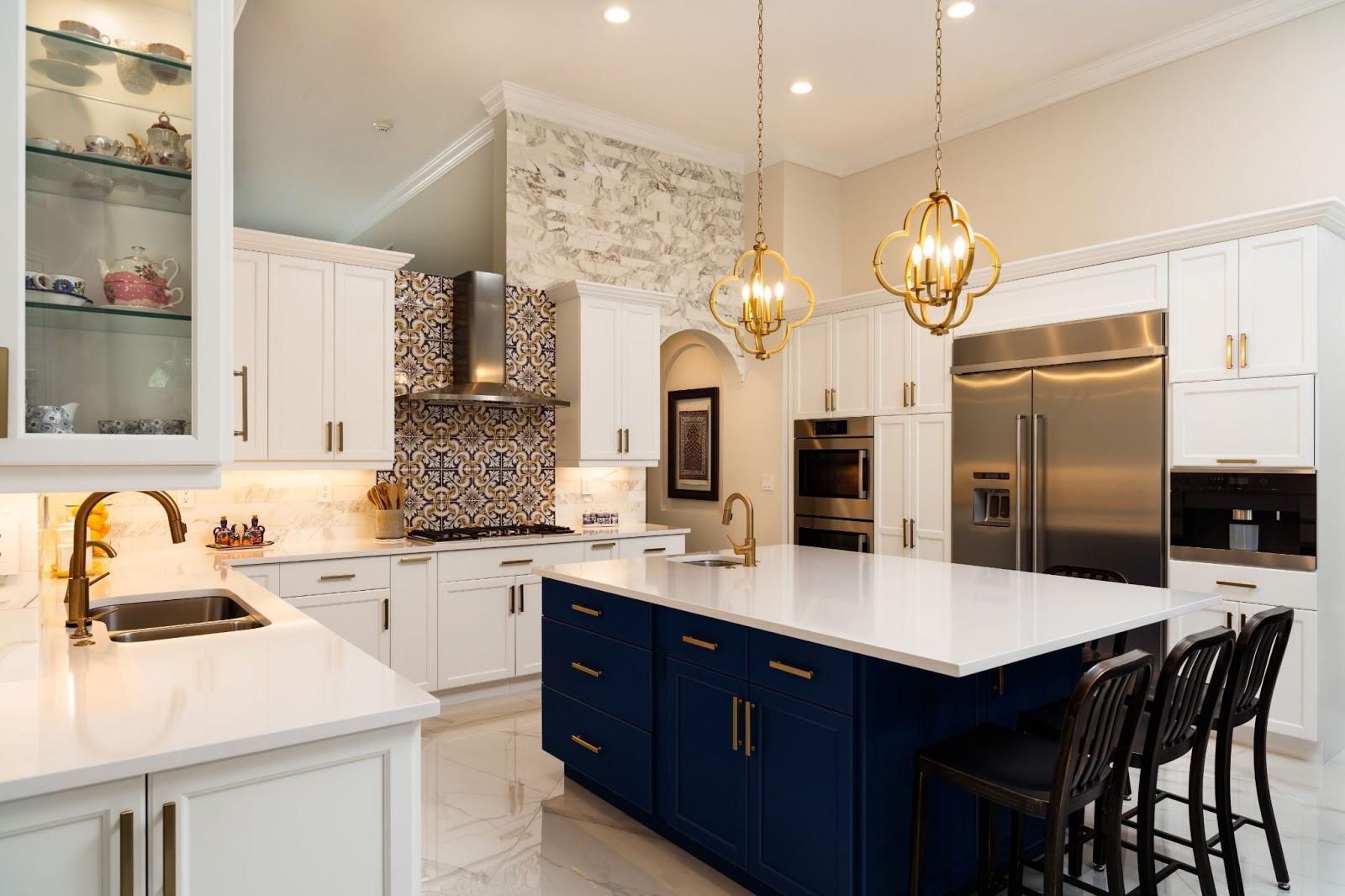 luxurious kitchen with black and white cabinets, an island, and gold hardware